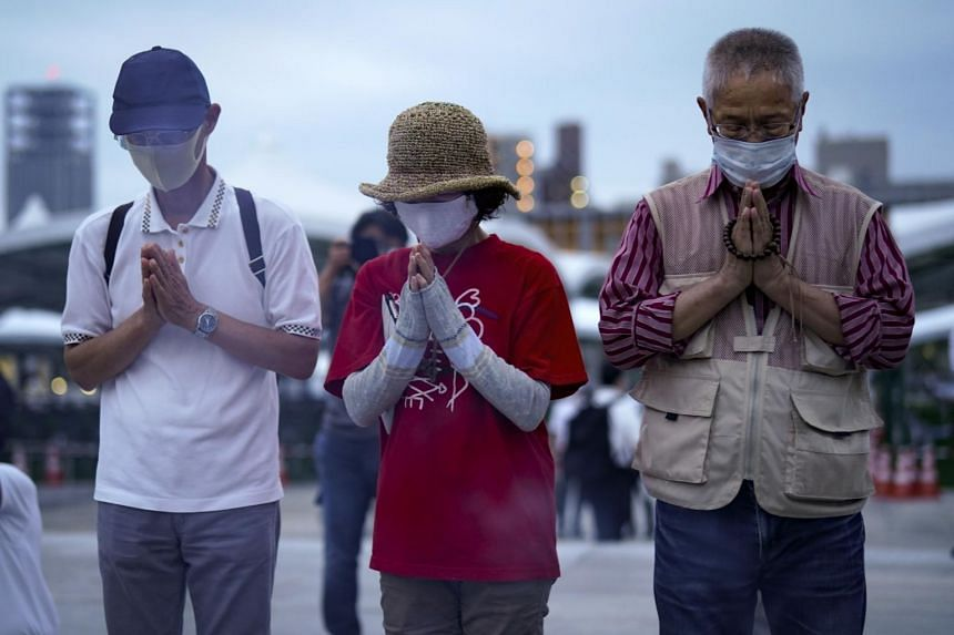 People pray for the victims in front of a cenotaph at Peace Memorial Park in Hiroshima on Aug 6, 2020.