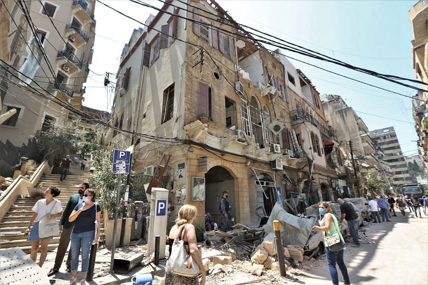People walk past damaged buildings at Achrafyeh Rmeil area after a massive explosion in Beirut, Lebanon, on Aug 5, 2020.