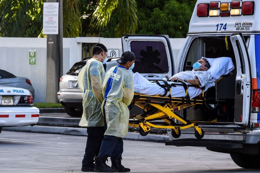 Medics transfer a patient on a stretcher from an ambulance outside of Emergency at Coral Gables Hospital near Miami, on July 30, 2020.