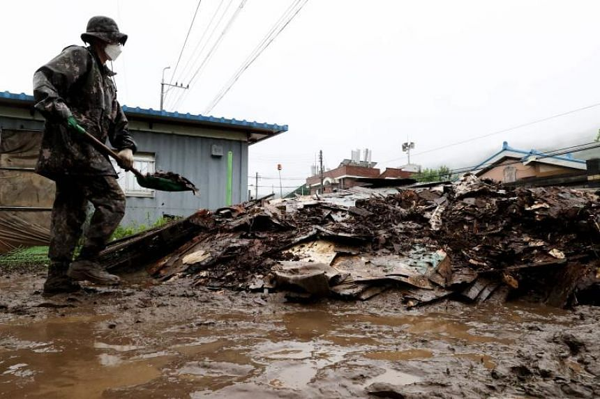 A soldier shovels debris left by flood damage in Cheorwon, a county next to the border with North Korea, in South Korea, on Aug 6, 2020.