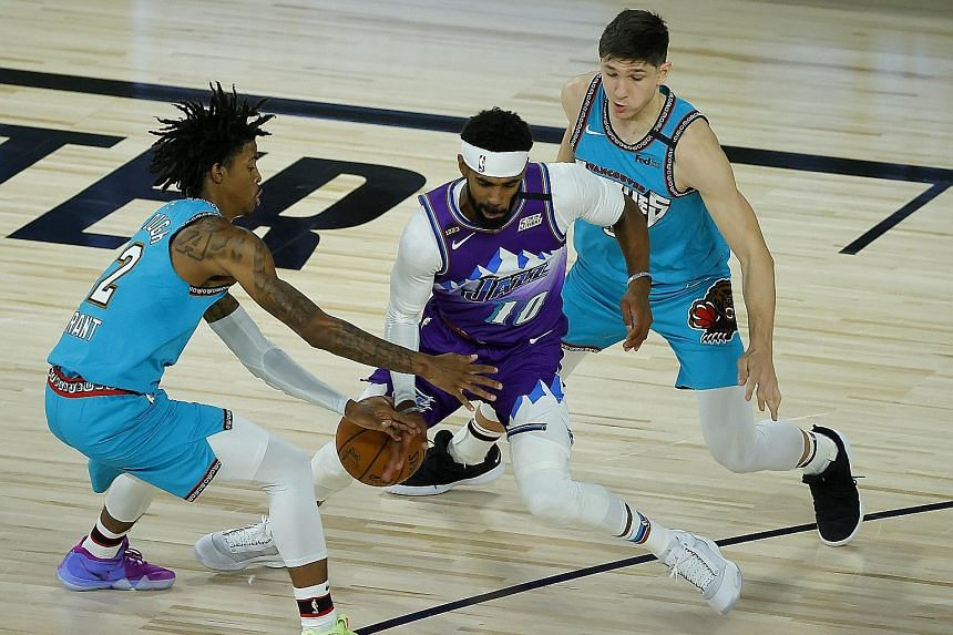 Mike Conley of the Utah Jazz comes up against the Grizzlies' Ja Morant (extreme left) as the Jazz clinched a 124-115 win at Disney World.