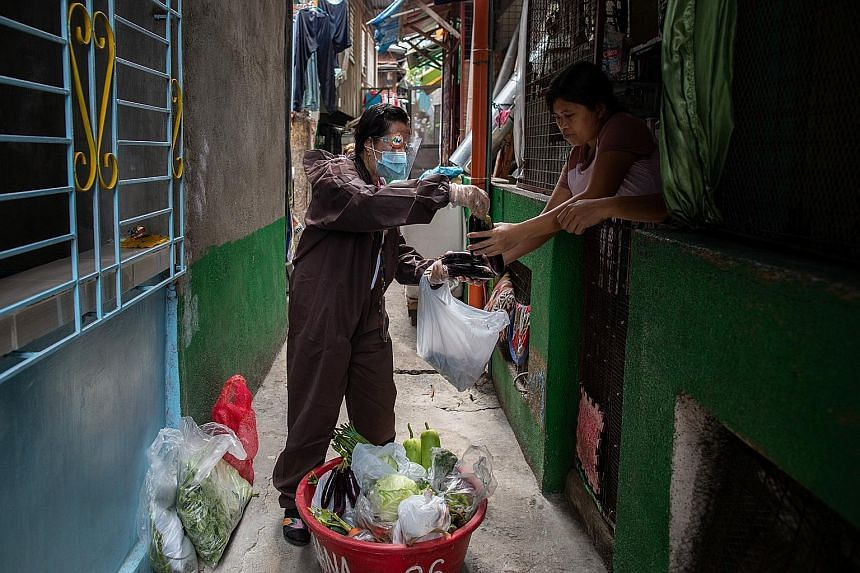 A government worker in a hazmat suit selling fresh produce in a neighbourhood in Navotas, Metro Manila, which is under a two-week lockdown starting from Tuesday. Philippines has recorded over 75,000 cases in June and July alone.