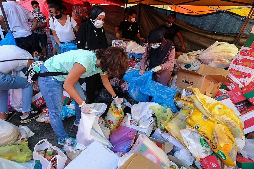 A spontaneous clean-up operation in a Beirut district hit by the explosion, which killed more than 130 people and wounded thousands. Anger against a government seen as corrupt and inefficient has risen. PHOTOS: REUTERS Volunteers packing aid supplies