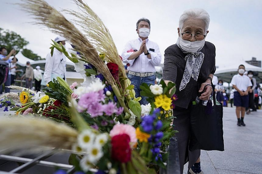 Though thousands usually pack Hiroshima's Peace Park on Aug 6 to pray and offer paper cranes as a symbol of peace, entry this year was limited and only survivors and their families could attend the memorial. PHOTOS: EPA-EFE An elderly woman (above) o
