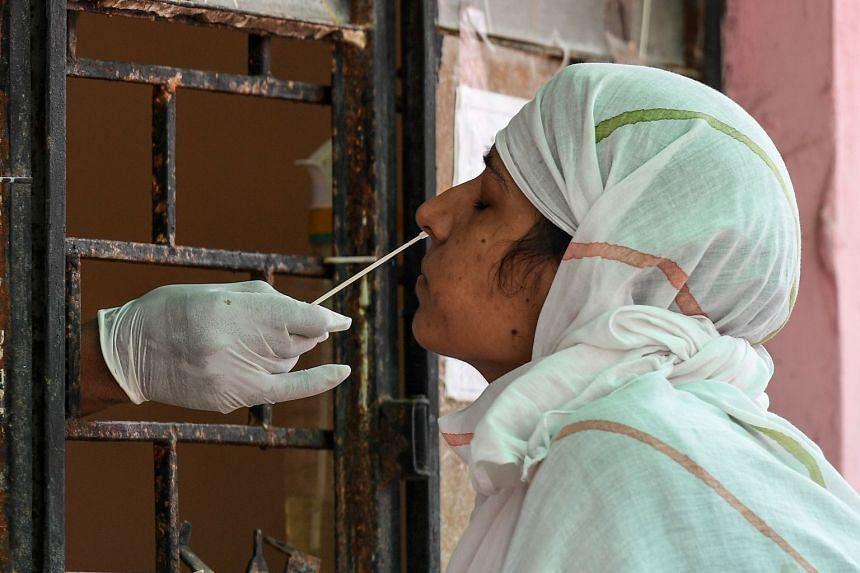 A women in India's Uttar Pradesh state undergoes a coronavirus swab test.