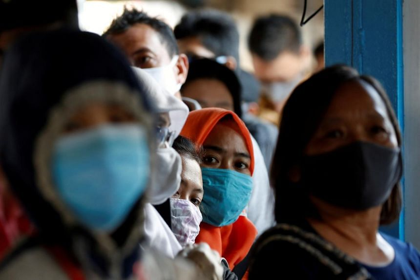 Passengers wearing face masks queue for a public bus in Jakarta on July 27, 2020.