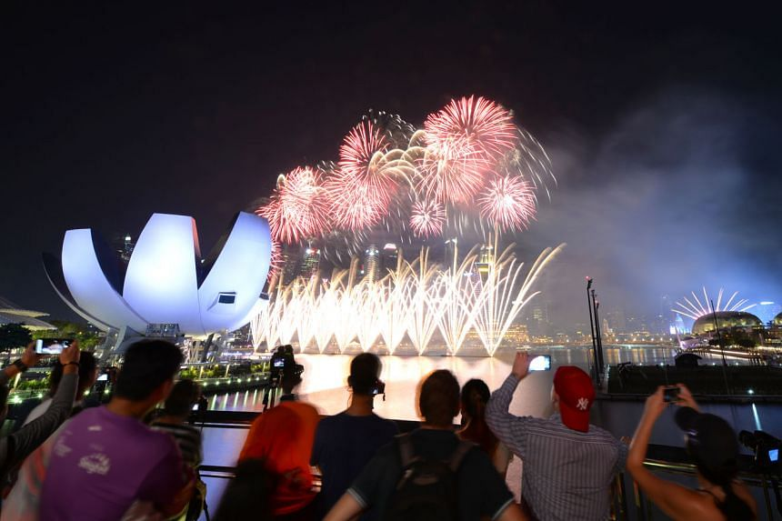"""The fireworks display for NDP2019, as photographed from the Helix Bridge. This year's fireworks will be launched at 10 different locations to """"share the NDP experience with as many Singaporeans as possible"""". ST PHOTO: SHINTARO TAY"""