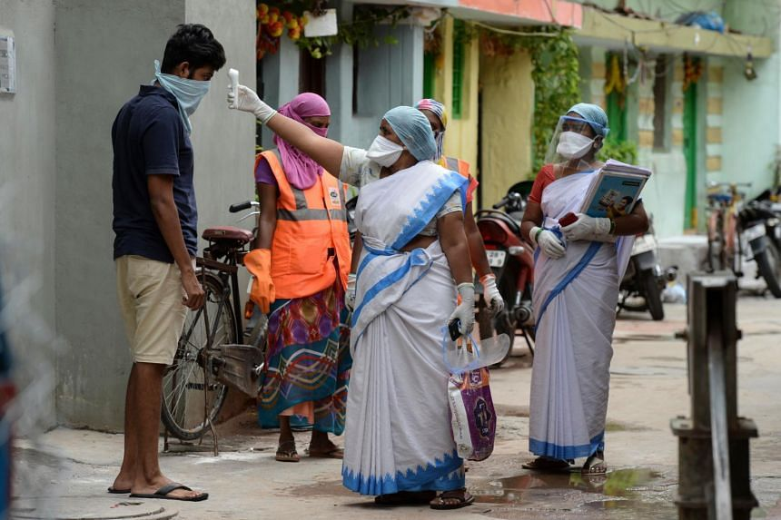 An Accredited Social Health Activist checks the temperature of a resident in Hyderabad, India, on June 30, 2020.