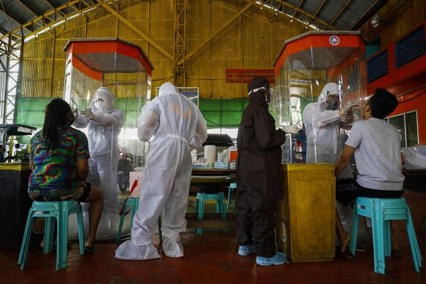 Medical workers collect swab samples for Covid-19 testing at a village in Caloocan City, Metro Manila, on Aug 3, 2020.