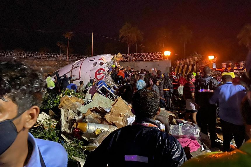 Officials inspect the wreckage, in a handout photo from the Indian Civil Defence.