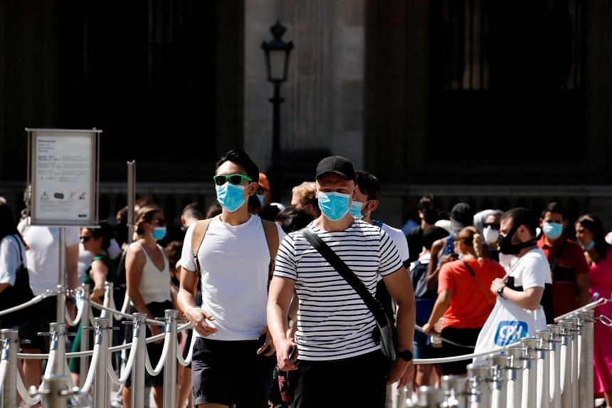 People wearing protective masks walk near the Louvre Museum in Paris, Aug 6, 2020.