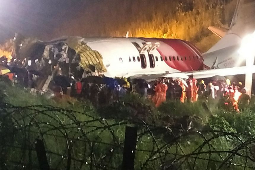 First responders gather around the wreckage of the Air India Express jet.