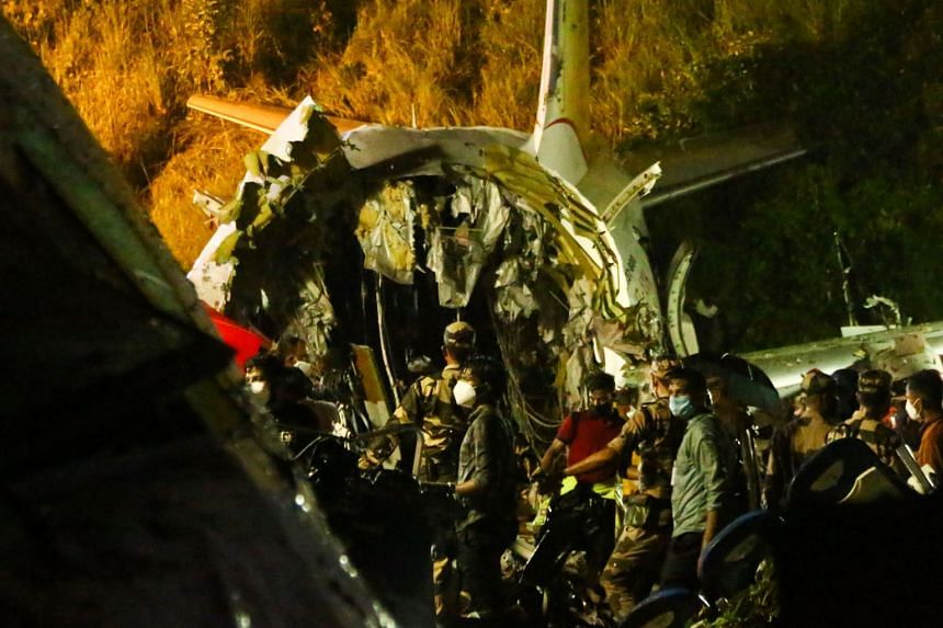 First responders inspect the wreckage of the Air India Express jet.