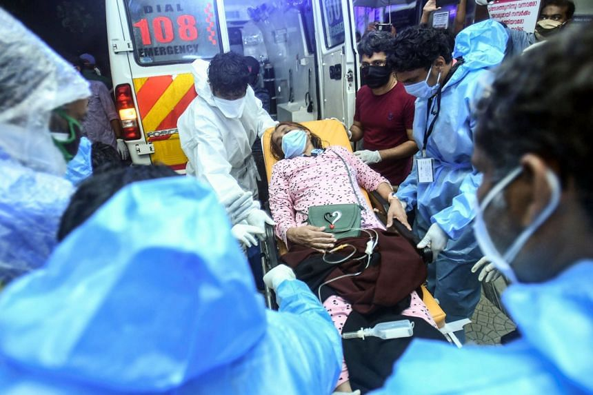 Health workers transfer an inured passenger on a stretcher to a hospital in Kozhikode, Kerela.