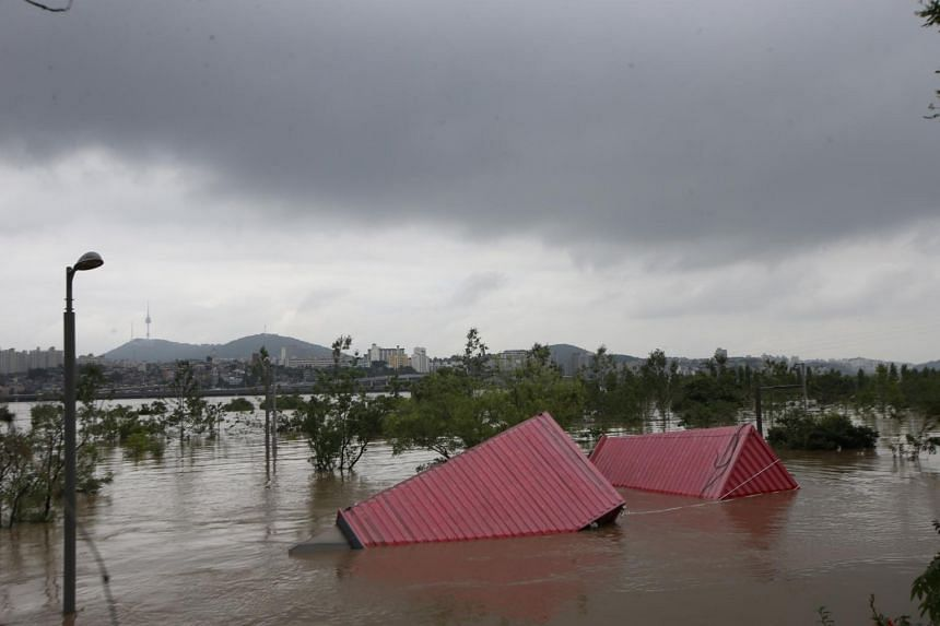 Containers get carried away by a flood in Seoul, on Aug 6, 2020.
