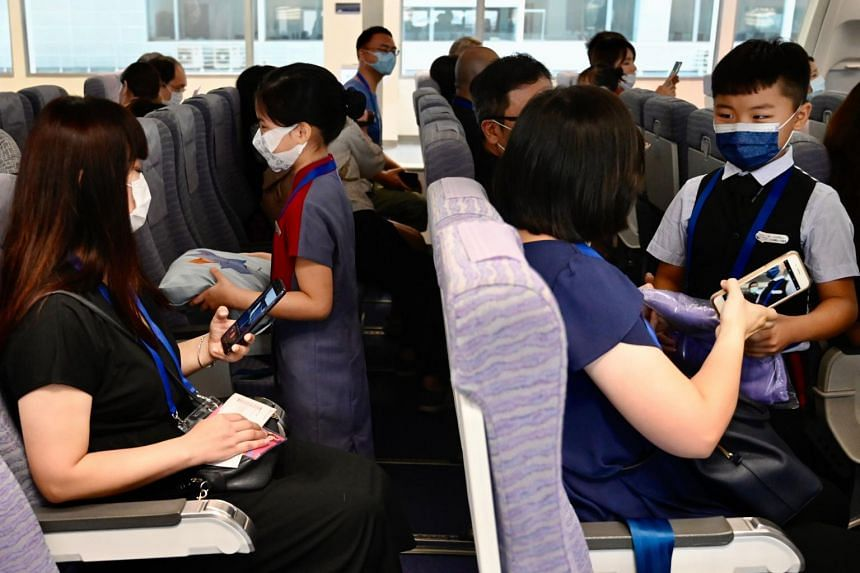 Children and their parents role-play aboard a mock cabin at China Airlines' headquarters in Taoyuan, Taipei, on Aug 8, 2020.