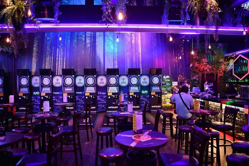 Forest Darts Cafe has reopened its Downtown East outlet but the approval process was onerous and costly, said co-owner Lena Sitoo. Few customers have returned as the darts and karaoke machines must remain powered down.