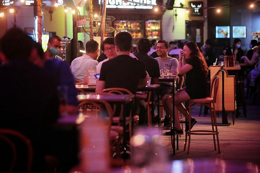 Restrictions on group sizes and live entertainment and a 10.30pm cut-off time for alcohol sales pose significant challenges, industry players say. Above: At Clarke Quay, temperature screening stations are positioned at four key entrances. Right: Abou