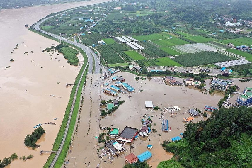 Left: A village submerged by overflow from the Seomjin River, due to two days of torrential rain in Hadong, South Gyeongsang province, in South Korea. Below: Residents waiting to be rescued from a market flooded by heavy rain in the south-eastern cou