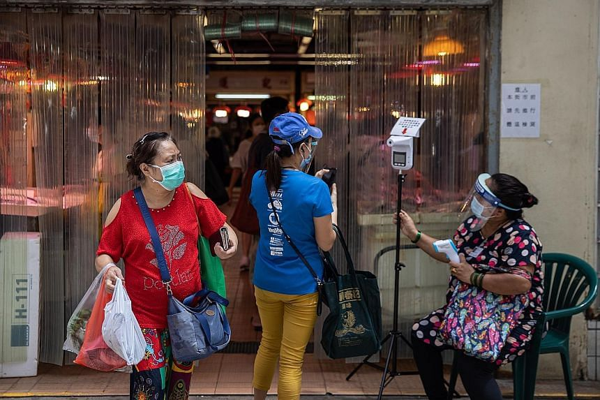 HONG KONG: Temperature screening outside a Hong Kong wet market on Friday. VIETNAM: Healthcare workers (left) spraying disinfectant at Vietnamese nationals after their Covid-19 repatriation flight landed at Can Tho Airport in the Mekong Delta region