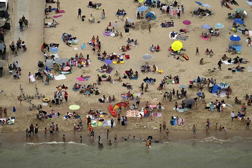 Tourists sunbathe at a beach in Oostende, Belgium, on Aug 8, 2020.
