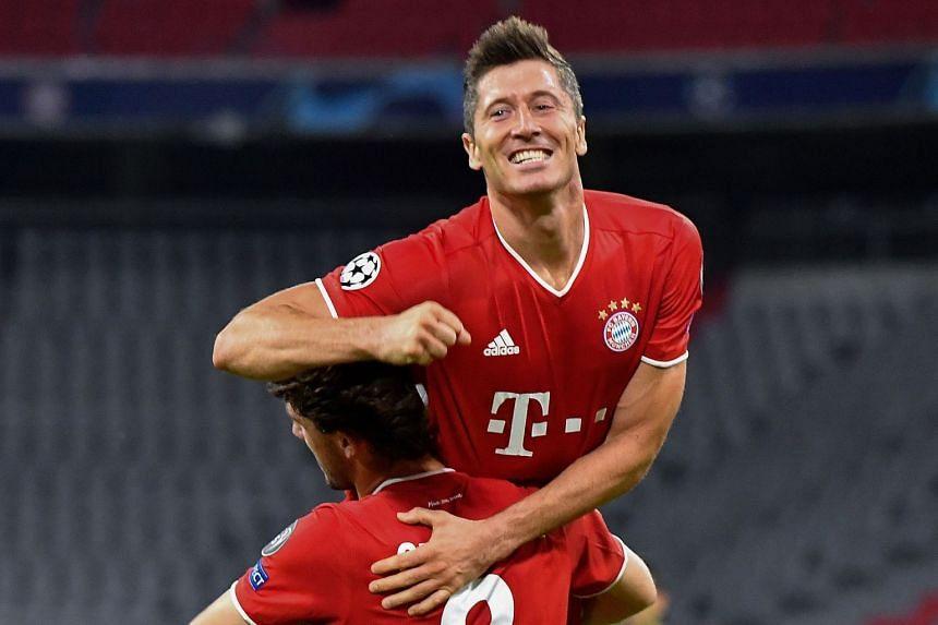 Bayern's Lewandowski (top) celebrates with teammate Alvaro Odriozola after scoring his team's fourth goal.