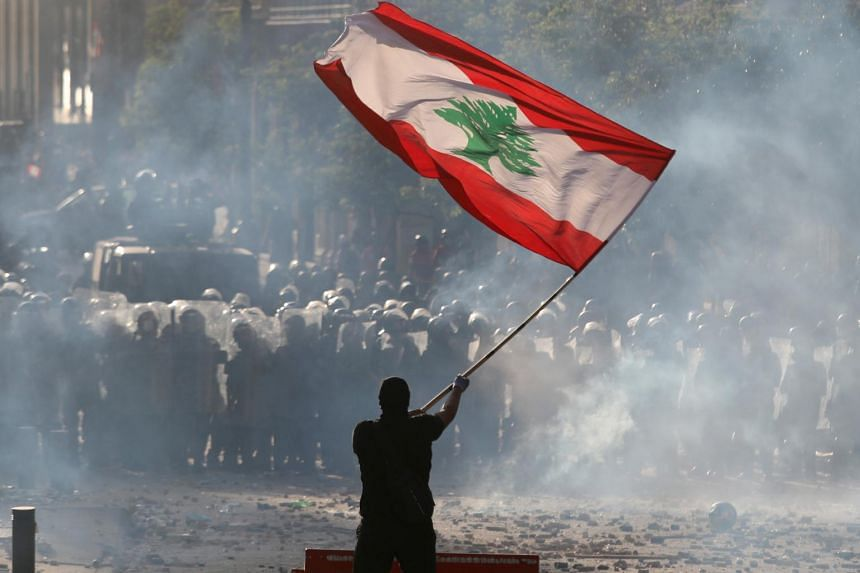 A demonstrator waving the Lebanese flag in front of riot police during a protest in Beirut on Aug 8, 2020.