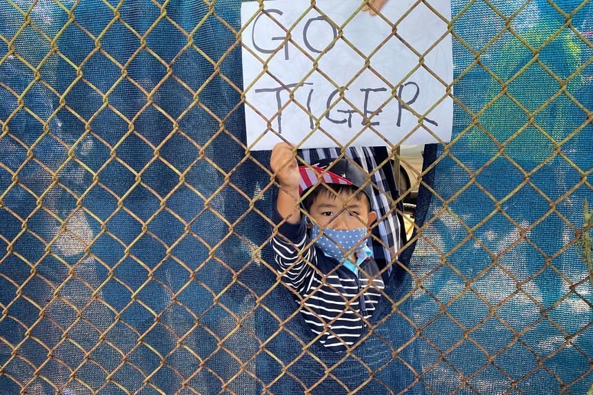 Tiger Woods supporters, like this young fan, peer through fences and climb ladders outside TPC Harding Park to cheer him on at the PGA Championship.