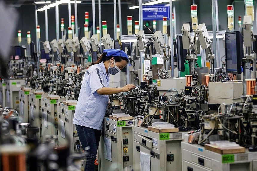 A worker making inductors for export in China's Jiangsu province last month. Industrial production growth is forecast to have picked up and retail sales may have stopped shrinking last month, in numbers due this Friday. PHOTO: AGENCE FRANCE-PRESSE