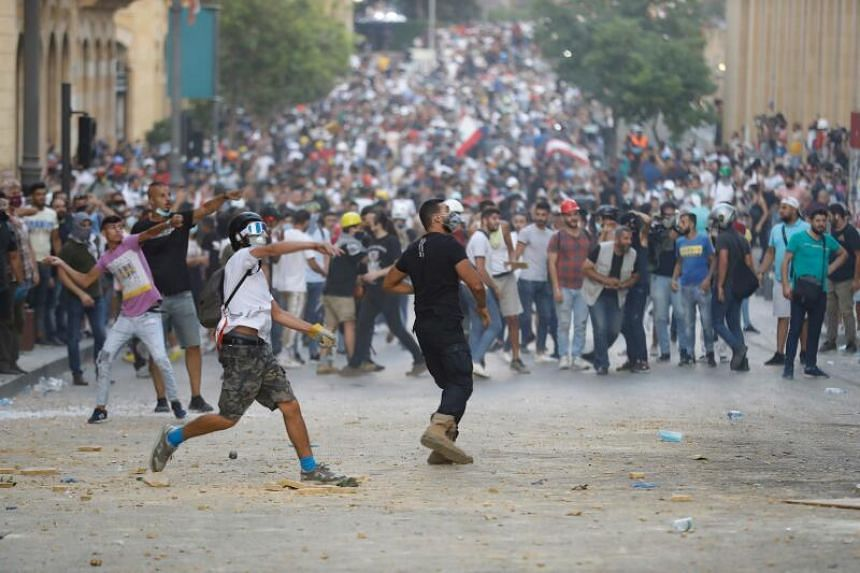 Protesters clash with Lebanese security forces near an access street to the Parliament in central Beirut on Aug 9, 2020.