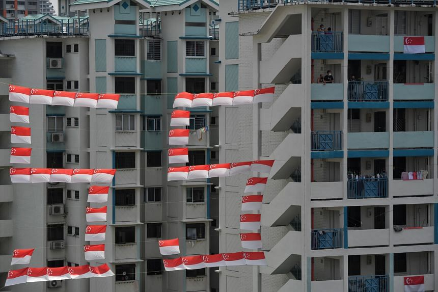 Residents awaiting the arrival of the mobile column outside their homes in Toa Payoh Lorong 1 yesterday. Next to them, national flags form the number 55, representing the nation's 55th birthday.