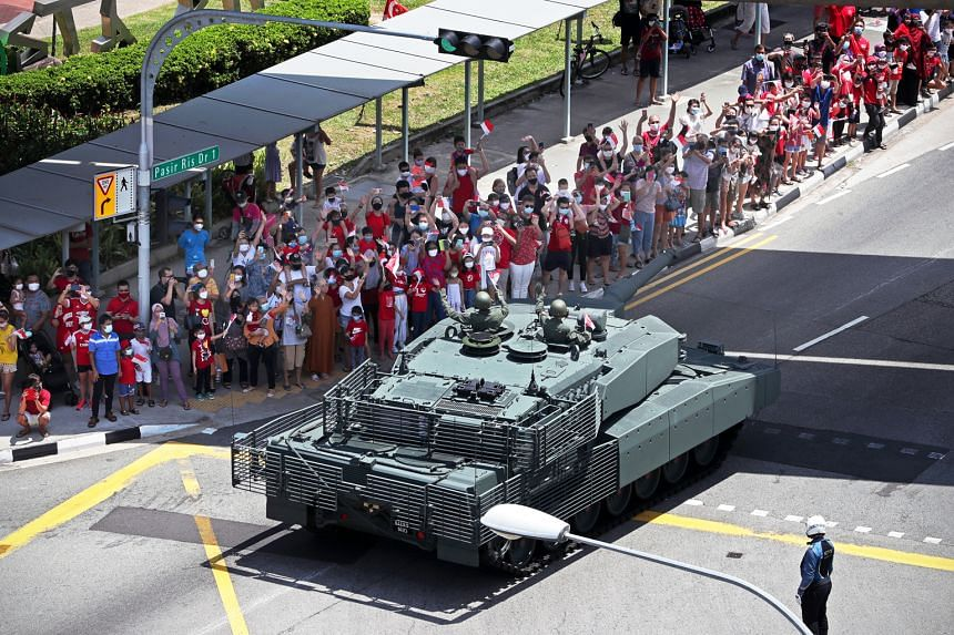 Spectators waving as the Leopard 2SG main battle tank moved past them in Pasir Ris Drive 1, along one of the five routes across the island taken by mobile column contingents.