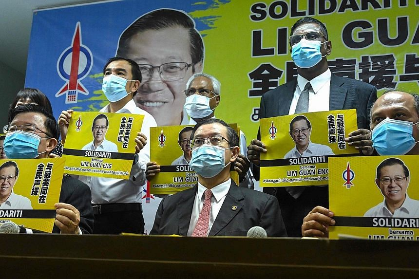 Malaysia's former finance minister Lim Guan Eng (centre) with his supporters during a meeting with the press in Penang yesterday, after being charged with receiving a bribe in connection with an undersea tunnel project when he was chief minister of t