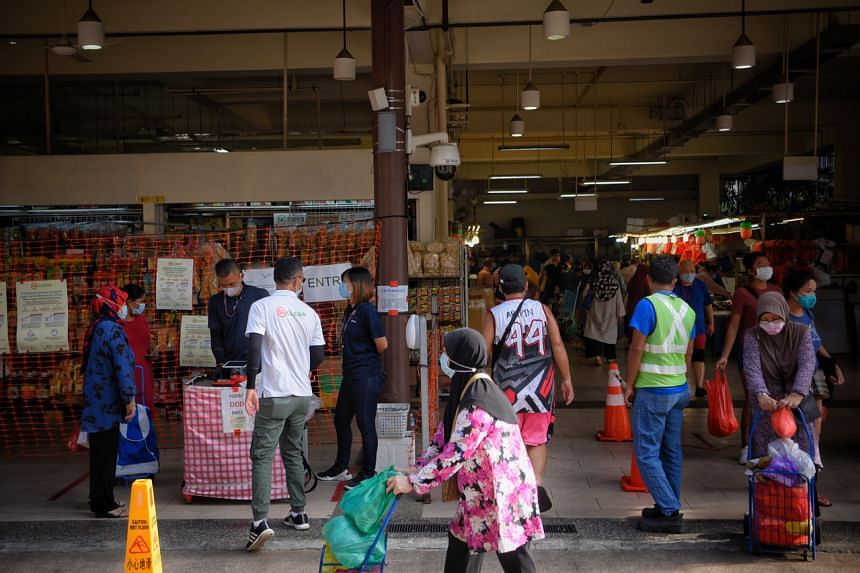 Auxiliary police check and scan the IC's of visitors at the Geylang Serai Market on Aug 7, 2020.