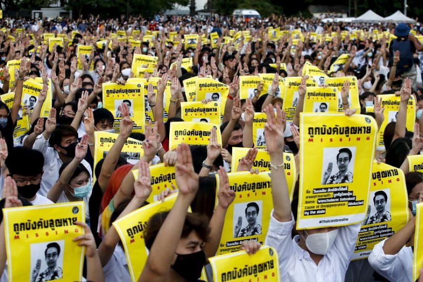 Pro-democracy protesters hold posters of missing activists and raising their hands in a three-fingers salute during an anti-government rally at Thammasat University in Bangkok, on Aug 10, 2020.