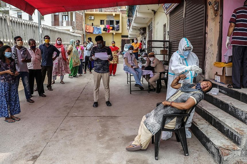 A healthcare worker collecting swab samples from a woman at a Covid-19 testing site in New Delhi yesterday. With more than two million cases, India has the third-highest tally worldwide after the US and Brazil. It took almost six months for the globa
