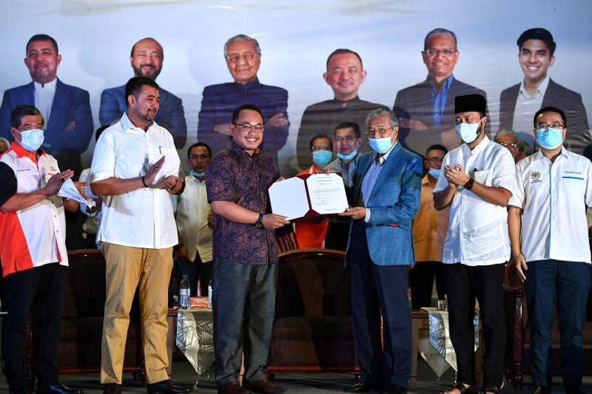 Dr Mahathir Mohamad (in blue jacket) handing a letter of appointment to lawyer Amir Khusyairi Mohamad Tanusi, on Aug 12, 2020.