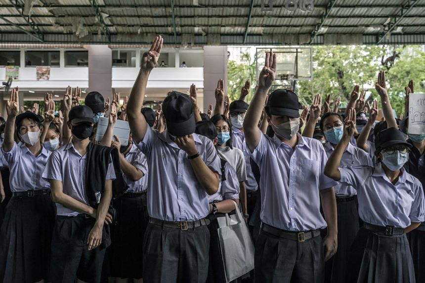 Students flash a three-fingered salute from the Hunger Games movies at a protest in Bangkok on July 31, 2020.