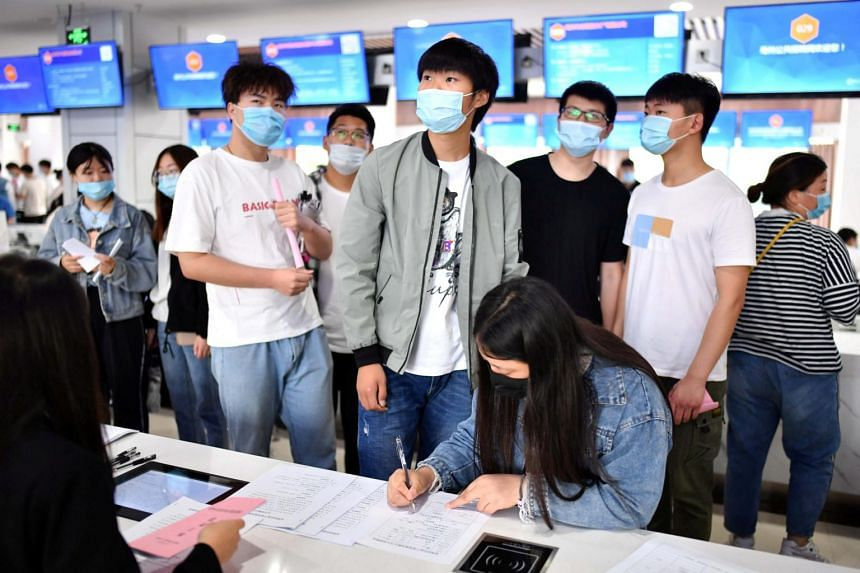 People wearing face masks attending a job fair for college graduates in Bozhou, Anhui province, on June 18, 2020.