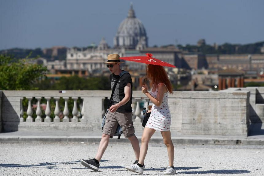 A couple shield themselves from the sun with an umbrella at the Villa Borghese Park, in Rome, on Aug 12, 2020.