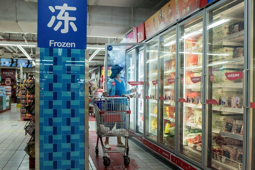 A woman looks at frozen food products in a supermarket in Beijing, China, on Aug 13, 2020.