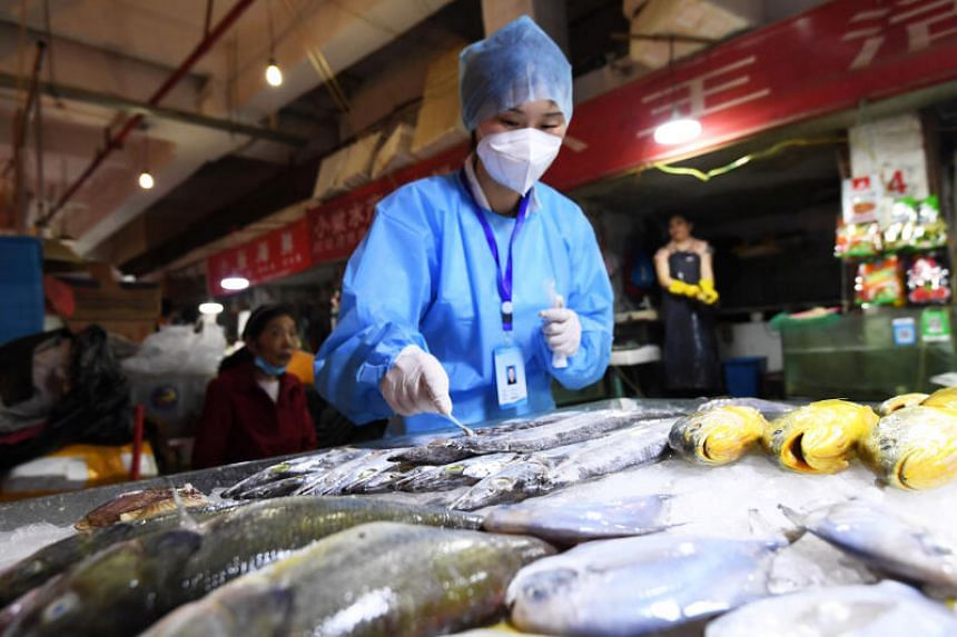 A health official collects a swab from frozen fish for testing at a market in Guiyang, China, on July 1, 2020.