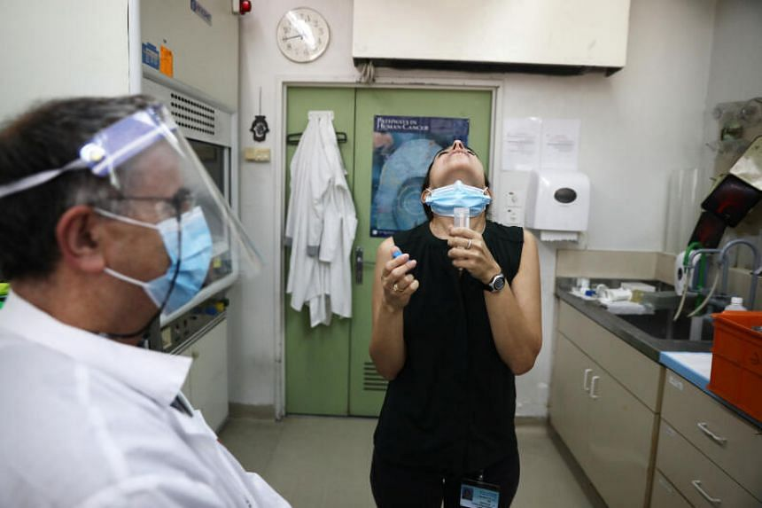 Patients rinse their mouth with a saline wash and spit into a vial.