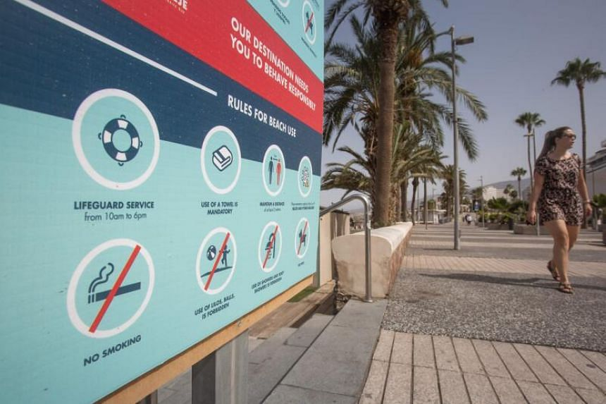 A woman walks past an information board about safety rules on the Canary Island of Tenerife, on July 28, 2020.