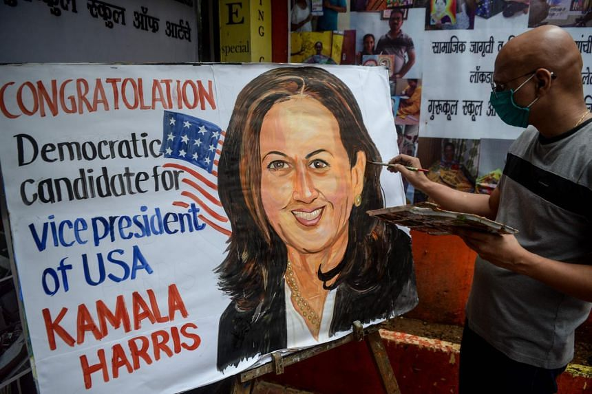 A man paints the face of presumptive US Democratic Vice-President nominee Kamala Harris outside a drawing school in Mumbai, on Aug 13, 2020.
