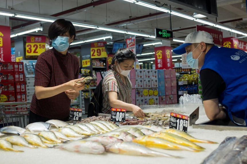 People look at fresh seafood in a supermarket in Beijing, on Aug 13, 2020.