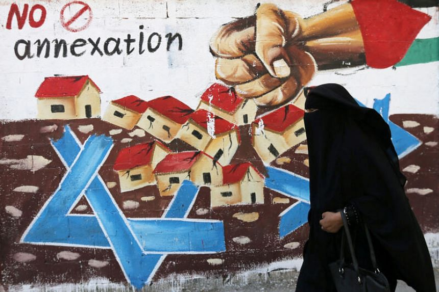 A Palestinian woman walks past a mural against Israel's plan to annex parts of the Israeli-occupied West Bank, in Rafah in the southern Gaza Strip, on July 14, 2020.