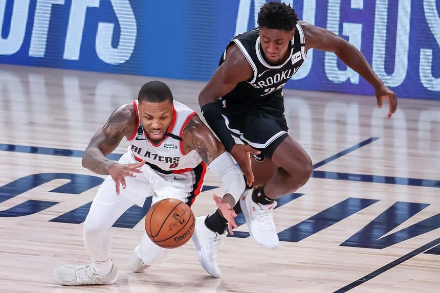 Portland Trail Blazers' Damian Lillard (left) makes a steal from Brooklyn Nets' Caris LeVert at the ESPN Wide World of Sports Complex in Florida on Aug 13, 2020.