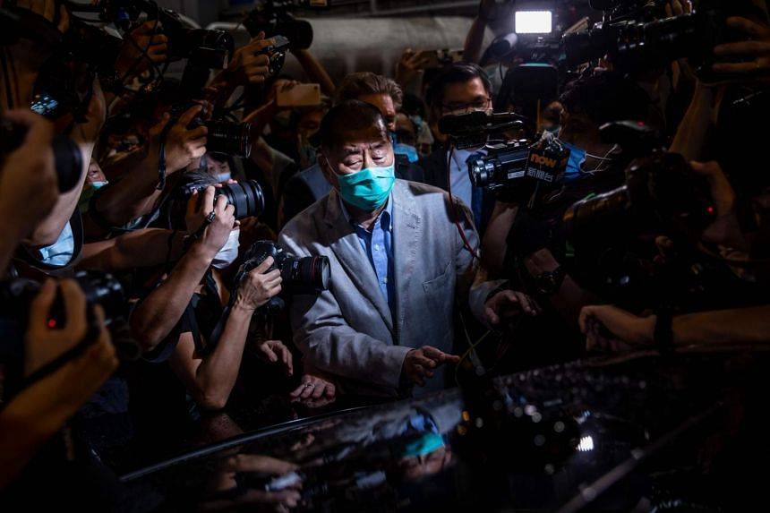 Hong Kong pro-democracy media mogul Jimmy Lai (centre) walks to a waiting vehicle after being released on bail from the Mong Kok police station on August 12, 2020.
