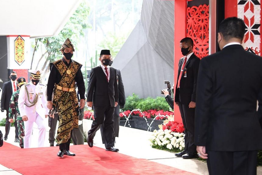President Joko Widodo (left), dressed in a traditional outfit from East Nusa Tenggara, arrives at a general assembly at parliament in Jakarta, on Aug 14, 2020.